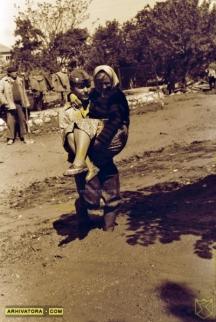 Войник пренася възрастна жена през оловно-цинковата тиня заляла Враца