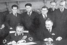 Георги Димитров и Йосип Броз Тито подписват договор за сътрудничество между България и Югославия. Зад Димитров е застанал вицепремиерът Трайчо Костов. Най-вдясно на снимката е Кимон Георгиев