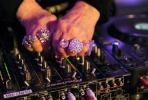 Обсипаните с пръстени ръце на 71-годишната диджейка не спират да работят на пулта за миксиране на звука